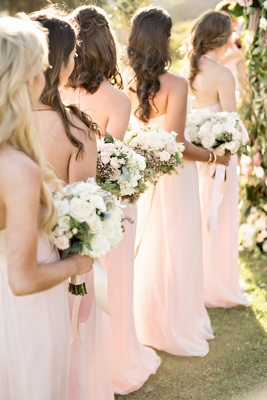 bridesmaids pink dresses lined up bouquets white pink flowers greenery chiffon fabric wedding