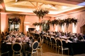 reception space with black linens and black and gold chairs, dark purple florals.