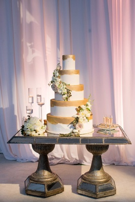 Gold paint brush stroke wedding cake decoration with fresh flowers and gold leaves