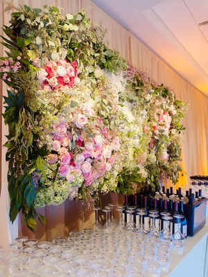 Weddng reception bar drink station decor flower wall greenery wine glasses and bottles