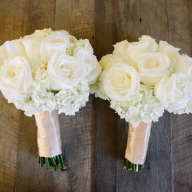 Two white rose, hydrangea nosegays wrapped in pale pink ribbon for bridesmaids