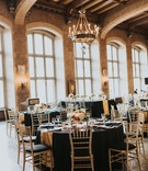 vintage chandelier above black and gold wedding reception table