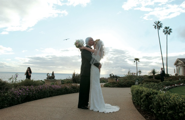 Bride and groom kiss on grounds of Montage Laguna Beach