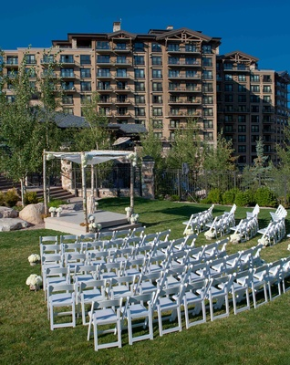 White ceremony chairs on lawn of Park City resort