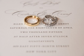 two wedding bands one gold one diamond atop couples wedding invitation with engagement ring