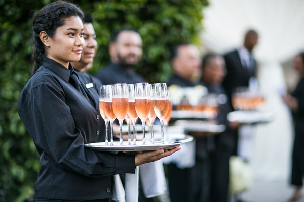 Cocktail hour servers ready to serve champagne and rose served on silver tray at outdoor wedding