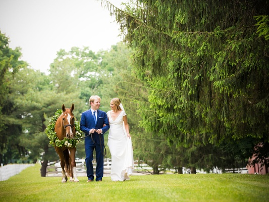 Groom in navy blue suit and tie with bride in sheath wedding dress v neck cap sleeves horse wreath