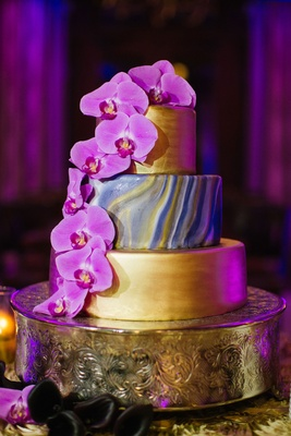 Wedding cake three layers with fresh fuchsia orchid flowers gold layers and marble design in center