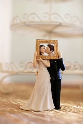 Wedding cake topper with groom kissing bride in gold frame