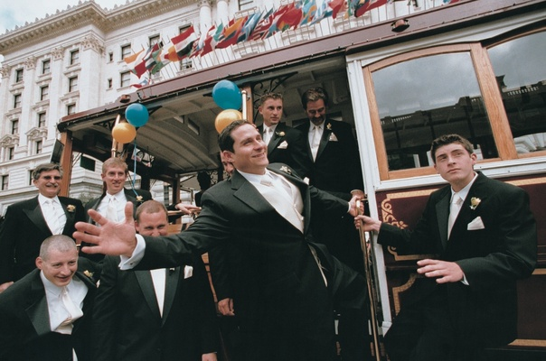 groom and friends take trolley car to wedding