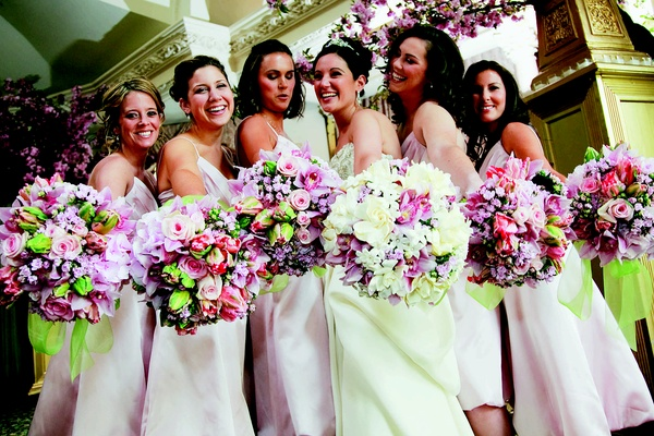 Bride with a bouquet of white, pink, and lavender flowers and bridesmaids holding pink and lavender