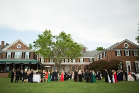 Wedding guests on grass lawn in front of brick country club