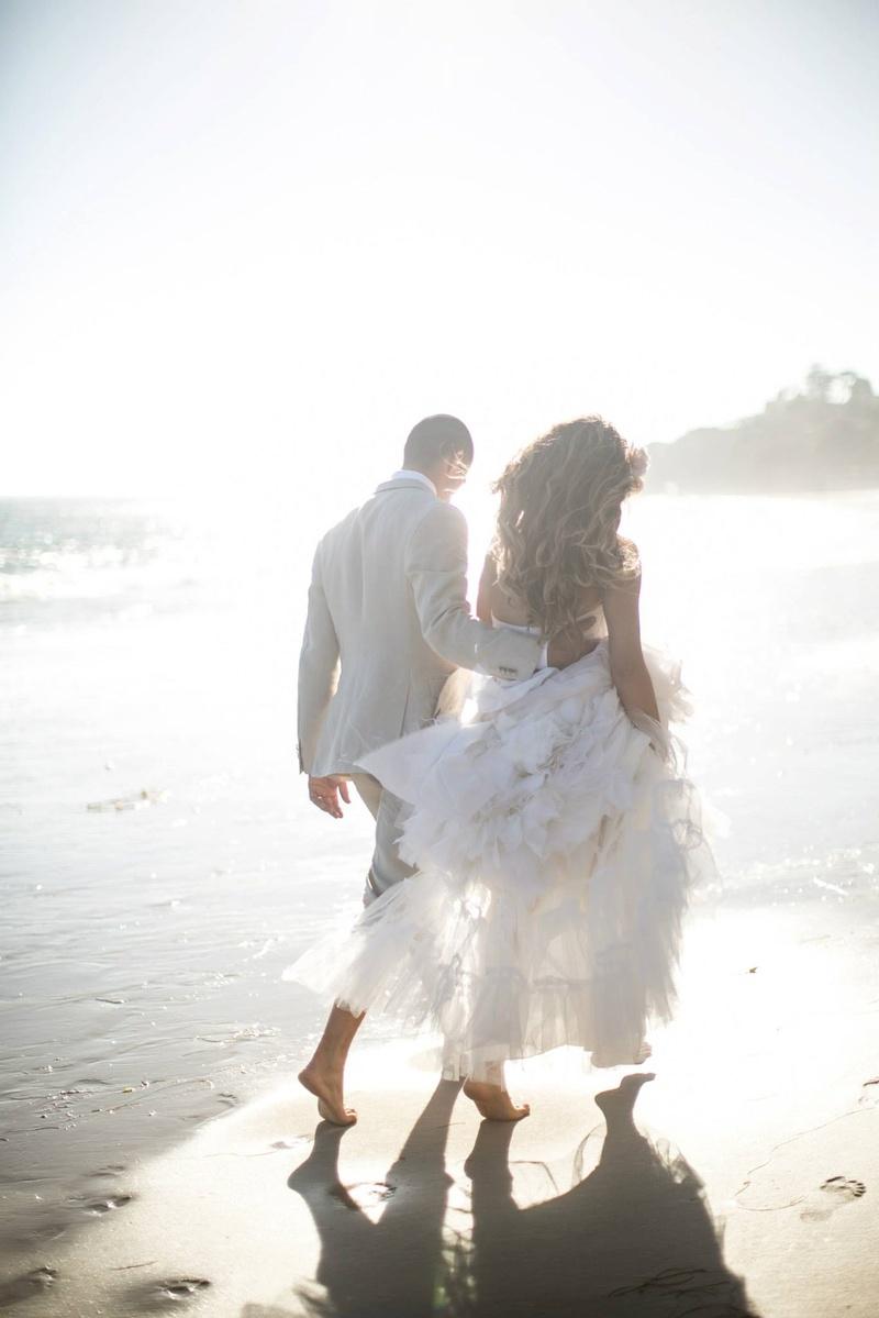 Katrina Hodgson and Brian Scott walk on beach in wedding dress
