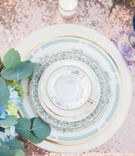 pale blue and gold china, rose gold linens, gold flatware, blue glassware colored