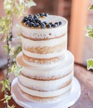 Semi naked wedding cake blueberries and gold details vanilla almond pistachio crumbs on wood