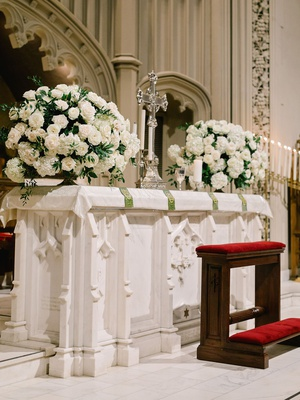 traditional church wedding ceremony altar with white hydrangea rose greenery flower arrangements