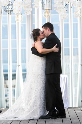a bride in white fit and flare gown and groom in all black tuxedo embrace first kiss married couple