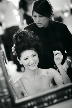 Black and white photo of stylist arranging bride's hair