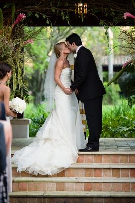 Bride and groom kissing on brick tile steps