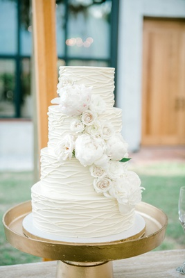 wedding cake four layer white cake with white rose and peony flowers gold stand textured