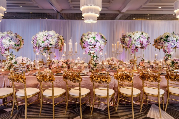 Wedding reception long table decoration ideas candelabra tall centerpiece gold chairs ruffle backs