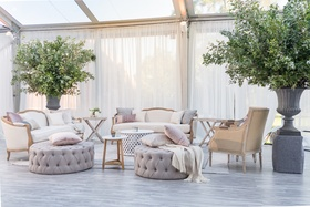 lounge area in soft neutral colors, grey quilted ottoman, displays of greenery