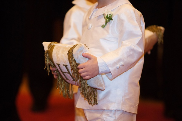 Ring bearer in white outfit holding ring pillow with monogram embroidery and fringe on both sides
