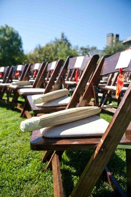 Paper parasols are set on chairs for an outdoor wedding