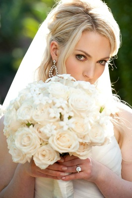 Blonde bride holding bouquet in front of face with natural makeup