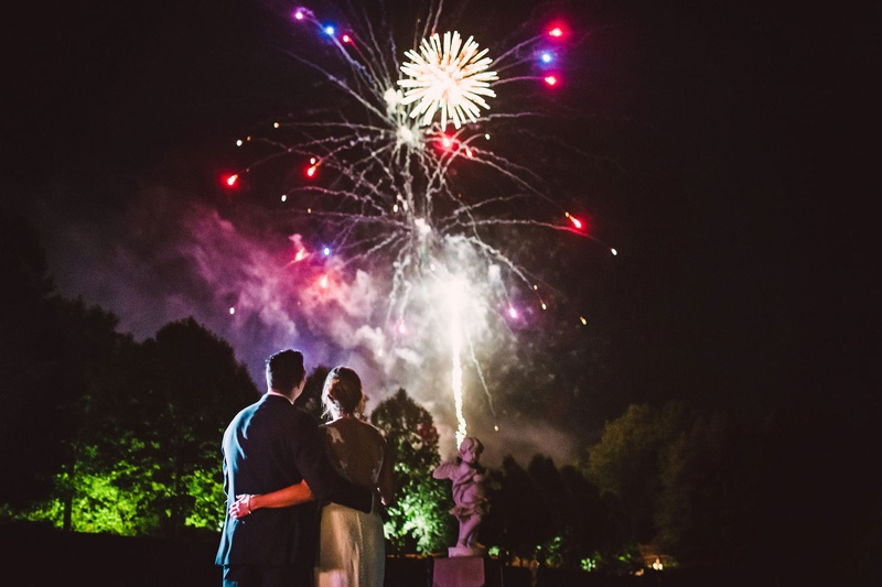 Bride and groom hug while watching firework show purple pink fireworks reception ideas entertainment