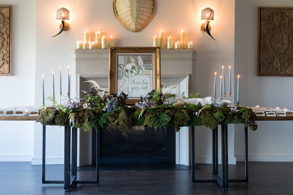 wedding reception escort card table french bulldog painting taper candles greenery candles fireplace