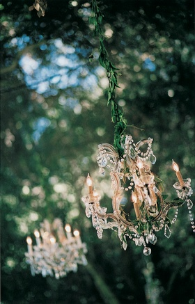 Chandelier wrapped in garland hanging from tree