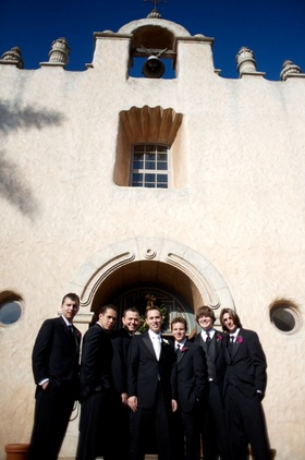 Groomsmen in front of mission style church