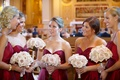 Bridesmaids in red dresses hold bouquets of light purple roses in church