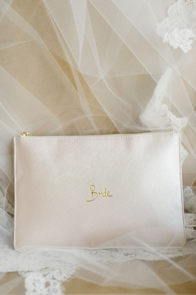 wedding accessories leather clutch with gold bride and zipper on chair with veil
