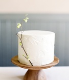 simple single tier cake on wooden stand with a sprig of corylopsis