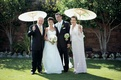 wedding couple with parents holding parasols
