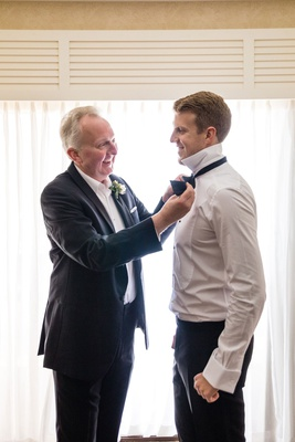 father of the groom in suit helping son get ready put on bow tie in groom's suite