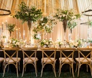 Long king's table wood chairs tall flower arrangements short high low rustic chandeliers drapes