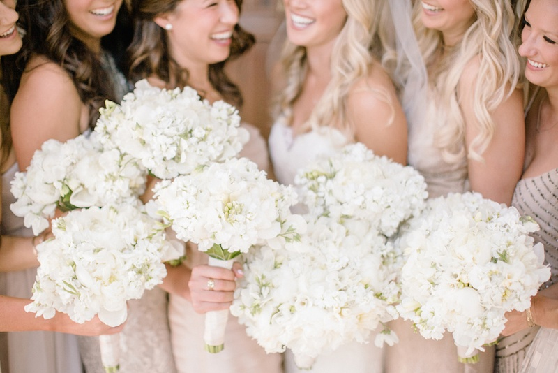 Bridesmaid with neutral dresses and bouquets of white peonies, sweet peas, freesias