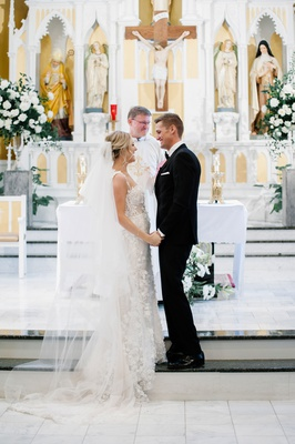 wedding ceremony bride in berta wedding dress groom at altar with officiant church in denver parish