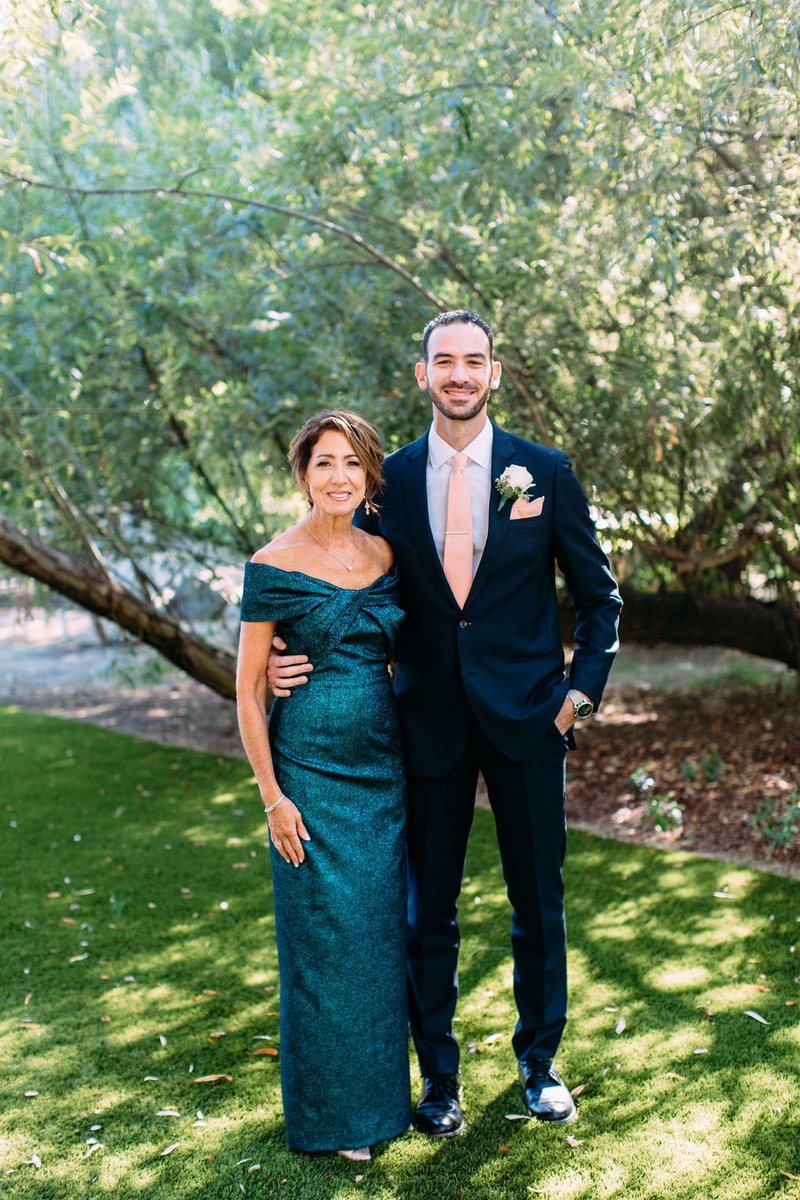 groom in suit with pink tie and mother of groom in off shoulder teal blue green gown