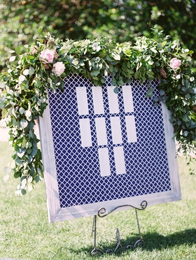Blue and white geometric pattern print in greywash frame greenery on top seating chart easel grass