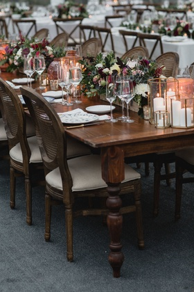 wedding reception wood table no linens low centerpiece fall flowers brass candle votives vase cane
