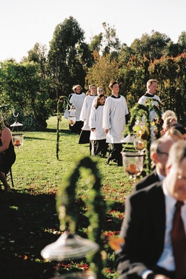 Church choir members perform in white robes at wedding