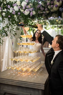 bride in martina liana groom in hugo boss pour champagne into champagne tower