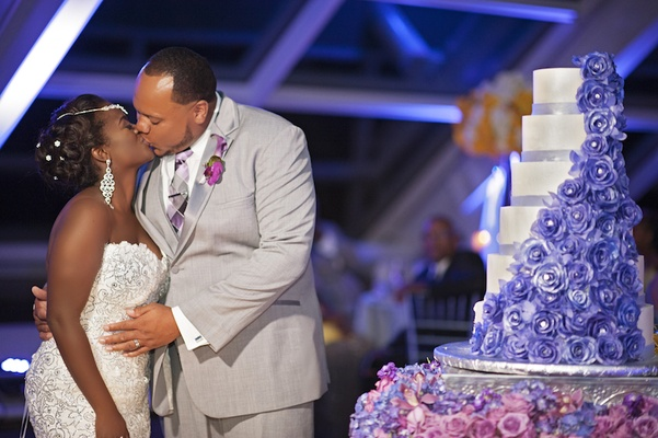 Bride in a spaghetti strap Pnina Tornai beaded dress kisses groom in grey suit, purple orchid
