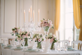 Wedding reception table with high and low arrangement of pink roses, lisianthus, white anemones