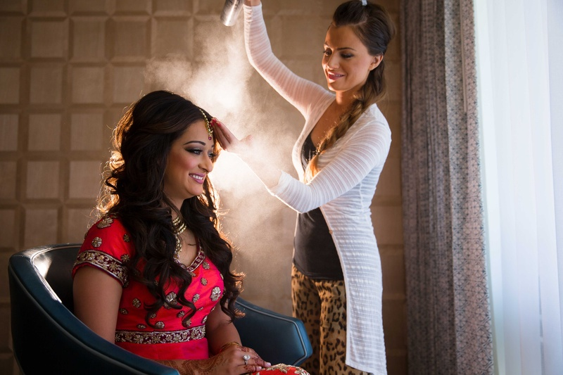 Hair Stylist Sprays Hairspray On Indian Brides Curled Wedding Hairstyle