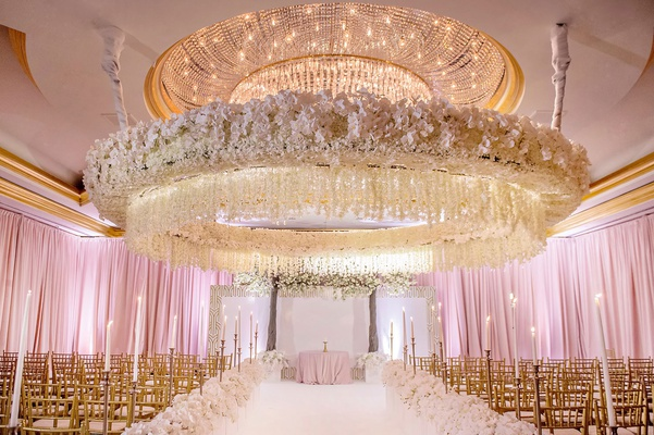 wedding ceremony circle flower ceiling arrangement gold chairs pink lighting drapery white flowers